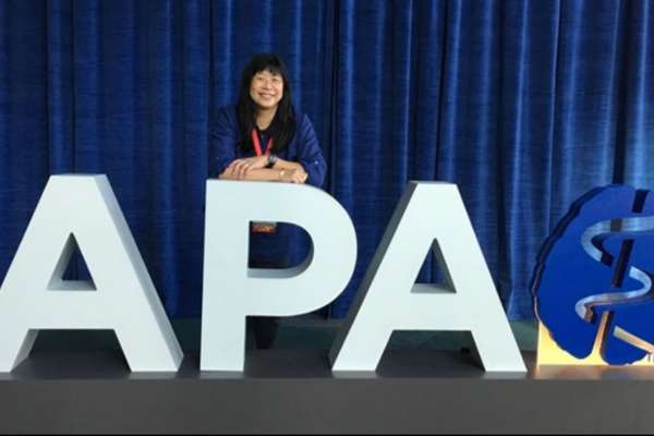 Dr. Cheong posing with the APA sign