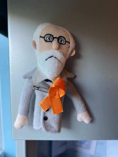Sigmund Freud doll wearing orange ribbon